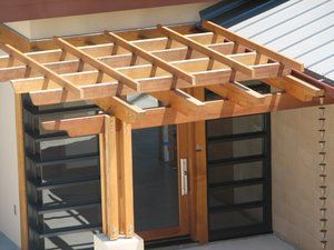 This front door entry structure was designed to emphasize the owners desire to show his appreciation for natural wood features that are in evidence throughout the entirety of the homes interior. All of the wood is cedar, custom milled and is nail free. All fasteners are stainless steel lag bolts with the vertical supports anchored onto a 18''x18'' concrete pedestal. the rain chain to the right eliminated the need for a distracting rain gutter down spout.