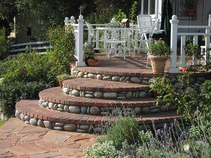 There is a little bit of everything here. The sidewalk is covered in a mortared in place Arizona mixed colored flagstone. The vertical faces of the steps are veneered in a cultured cobble stone and treads covered in used clay brick.