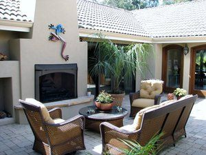 Residential courtyard with a tumbled paver surface. The pavers are composed of 2 different sized rectangles and placed upon a 10'' base of 3/4'' granite to allow problematic subterranean moisture to flow through. Fireplace hearth is capped with a Arizona flagstone. Fireplace is built in place (not prefab) of concrete masonry block.