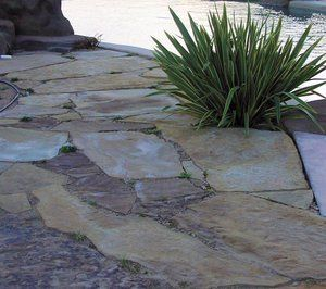 The flagstone pictured here, Called ''Cherokee Creek'' is laid upon a standard 4'' thick compacted class 2 base. This was used in lieu of a concrete pool deck to provide a permeable surface for runoff from a slight slope adjacent to the pool. To soften the appearance of the stone, Small clumps of a very low water use grass, Carex caryophyllea 'The Beatles', was planted in some of the joints as well as a Phormium 'yellow wave'.