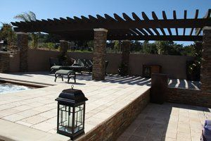 This is the same project pictured earlier but the emphasis is on the Plastered walls & the travertine paver deck. The travertine was a 12''x12''x1'' paver material from Mexico and wall laid upon a 6'' deep bed of compacted 3/4'' crushed granite. Following the travertine installation the joints were filled with a polymeric sand that is electrometric therefore eliminating cracking. The steps leading to the upper deck are capped with the same material as seen in A5 & 6. At each step location embedded louvered LED lighting was installed.