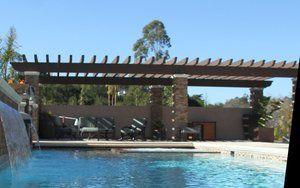 Originally this pool was to have a cabana but when the local HOA would not approve a solid walled/roofed structure this became the alternative. In order to integrate some of the materials found on the home we constructed the columns out of 18'' CMUs and poured them solid with concrete. Following the that each column was covered in a quartzite stone veneer with each corner piece cut at a 45 degree angle to provide a very finished looking 90 degree corner. Each column is finished with a poured in place ''white Portland cement'' cap with a 2'' bullnose radius. The two headers are custom ordered 4x12'' laminated beams with 4''x8'' cross members placed on edge.