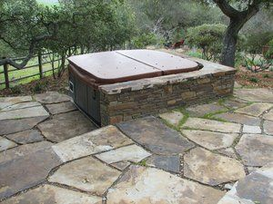 Portable spa with a  three sided block wall that is veneered in 'pencil rock' and capped with ''Lincoln'' flagstone. The patio area is composed of more Lincoln flagstone with each piece cut to provide a even joint between each stone. In the deep shade under the oak tree, ''Irish'' moss was used to fill the joints with the majority of joints filled with a recycled chipped stone.