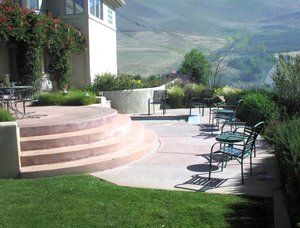 A traditional poured in place step and patio adjacent to a small spa. The flatwork is stamped to match the flagstone coping around the spa as are the steps leading down from the upper patio. Now days we tend to discourage the use of this much concrete due to the cracking and its impervious nature. Favoring pavers and concrete alternatives.