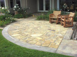 Cherokee Creek flagstone, each individually cut to form uniform grout joints with colored grout to match the surrounding band of concrete. The same flagstone was used to construct stepping stones and pathways throughout the property.
