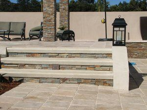 Close up detail of the travertine pavers, stone veneer and embedded step lighting.