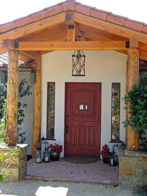 Rustic front door entry, featuring lodge pole posts, mounted on raised stone veneered bases. Porch floor is tiled with 1''x1'' tile mosaic.