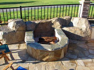 Fire pit is constructed with concrete block that is covered with a ''gold dust'' quartzite flagstone on the vertical surfaces and capped with a contrasting bullnosed quartz that was custom ordered. The Faux rock was hand shaped and stamped with stone textured latex mats, stained and sealed with a satin finish.