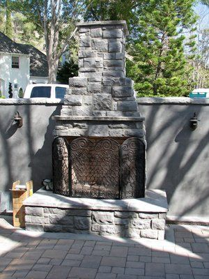 This fireplace is faced with faux stone veneer to blend with the stone used on the exterior of the wall and house. Plumbed for natural gas with a flagstone capped hearth.