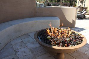 Natural gas fire pit set in a concrete urn with remote controlled and wind proof ignition system. Large recycled glass in-fill. Gas line was preplumbed and stubbed up through the travertine pavers. firebowl has a built in drain to allow rain-water to escape and not flood gas orifices. Fire pit area has a raised concrete surround to protect from the cool evening breezes that are a regular Los Osos Valley occurrence. The bench area is a separate concrete pour of white Portland Cement with a smooth trowel finish.