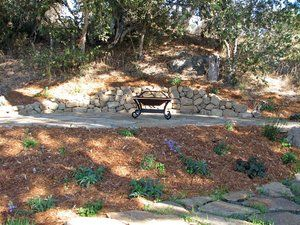 Very simple copper firepit adds rustic charm to a native flagstone patio and drystacked stone retaining wall. Due to the site location no gas line could be provided and transporting concrete or block up to the location would had to been done by hand so a low cost alternative was a light weight copper pot that would age well and require no maintenance. Fuel source is fallen oak branches.