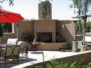 A concrete block wall breaks the prevailing on shore breezes and hide the parking area as well as  serving as the backdrop of the fireplace. The finish is a smooth ''Mission Style'' plaster with flagstone caps on the wall top and hearth.