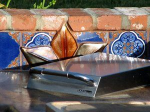 Outdoor kitchen backsplash detail with a warming burner in the foreground.