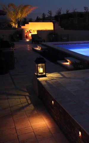 Embedded copper step lights illuminate the deck and steps with a candle powered fixture accentuating the travertine pavers.