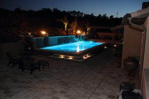 Travertine stone pavers are illunimated by the embedded lighting throughout the pool perimeter