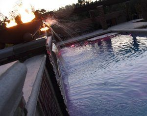 LWind catches the falling water as  the sun and firelight illuminate it.