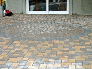 Circular tri-cobble pavers set within a field of rectangular multi-sized cobbles.
