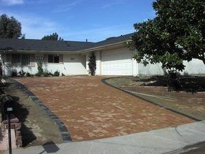 Original driveway removed and replaced with Roman 1 and 2 sized cobbles. Perimeter band is a charcoal gray rectangular paver.
