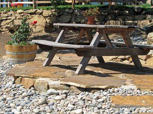 ''select'' grade Lincoln flagstone was used to create a level seating area under an oak tree with native stone debris used to construct a retaining wall. All the material used in the drystack wall was obtained when grading the area for the picnic table. The joints in the flagstone patio were filled with smaller debris pieces and mortared into place to provide added interest and reduce the amount of onsite waste.