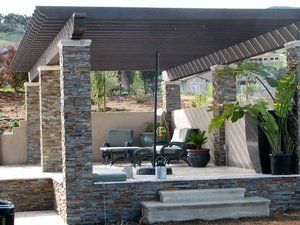 Seating area under arbor is paved with a 12''x12'' tumbled travertine paver set on a class 2 compacted base. Walls are retaining approx. 4' of soil allowing us to double the size of the backyard area and lower the elevation to help escape the prevailing on shore breezes that occur each day. The columns were constructed of concrete block, filled with concrete and veneered with a quartzite pencil rock for a mortarless appearance. Each column cap was setup with a Styrofoam form to allow for a bullnosed cap to be poured out of white Portland cement. The timbers are 6x12'' custom milled with 4x8 cross members.