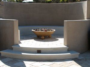 White Portland Cement steps lead up from a travertine paver deck and into a semi-private fire pit and conversation area. The steps were formed up using Styrofoam molds to create the cantilevered bull nose on each step. The back wall of the firepit was built higher than the surrounding walls to obstruct the view corridor into and from the neighboring property. The bench seating was formed up after the block wall was completed and was poured in place with a trowelled finish. The firebowl is a molded concrete product with built in drainage line and gas supply as well as a remotely controlled ignition system.