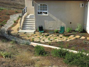 This was a ''problem area'' that a client wanted to deal with in a way that would eliminate persistent groundwater percolation problems that originated from an adjacent uphill property and still maintain an existing seating area that received the suns first rays of light each morning. The area had to be regraded and a concrete wall installed with a French drain to intercept the water prior to reaching the house. The French drain continued on around the house in the area below the cobbles. The flagstone area was then over excavated and filled with drain rock and wrapped in a geo-fabric to prevent soil migration into the drainage area.  Flagstone was laid on top with soil in the joints to allow thyme to eventually spread. Allot of work to drink your morning coffee in the sun.