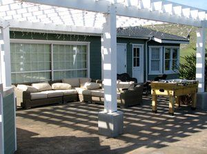 Outdoor living area adjacent to the pool. Deck area was constructed of stamped concrete with integral color that was highlighted with a colored release agent. Following a 28 day curing process it was then acid stained and sealed with a color enhancing finish. The arbor was needed to obstruct the summer sunlight, both on the deck and through the windows of the guest house. It was constructed of Paint grade Fir with all timbers either bolted or notched and fastened with teflon coated screws. All the raised footings for the posts were formed and poured with beveled angles on all corners/edges.