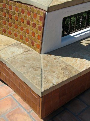 This outdoor seating and entertaining area has a Mexican tile similar to a satillo but rectangular instead of square. It was laid in a Herringbone pattern to eliminate the linear grout lines that would had resulted if the typical 12x12 tiles had been used which would had enunciated the already narrow deck area. The counter is topped with polished granite and is provided with both a gas grill and a stainless steel pit BBQ. Bench seating was built into the perimeter of the deck to allow for additional seating.