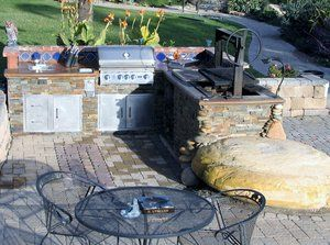 Custom Outdoor kitchen with a concrete counter top, gas grill & oak pit bbq.