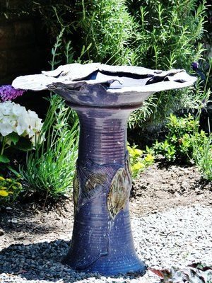 Enameled birdbath with copper highlights in a bird and butterfly garden.