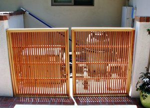 A pool equipment vault gate constructed of redwood 1''x1''s provides just the right amount of screening.