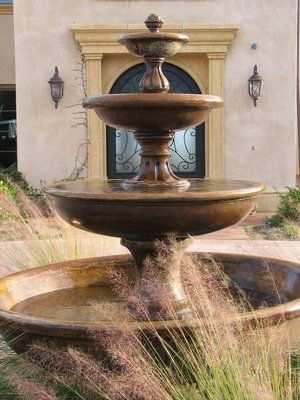 Old world 3 tiered fountain welcomes arrivals to the front door.