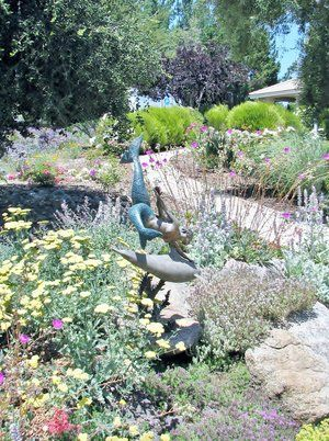 Mermaid sculpture mounted on boulder and used as centerpiece of perennial garden.