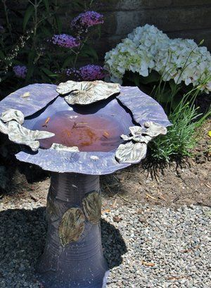 Hand crafted enameled sheet metal bird bath with acid stain ''high lights'' as focal point in a bird and butterfly garden.