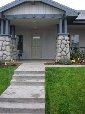 A Colored and stamped concrete walkway, in a flagstone pattern, lead up to the covered front porch flanked by cultured rock covered columns.