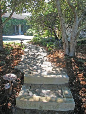 Flagstone path using stone that was quarried on site, produce a meandering pathway through a oak and manzanita grove. Pathway is illuminated using copper light fixtures that are in the shape of toadstools. The steps were retained with 6x6'' pressure treated timbers to increase their stability and still maintain the rustic appearance of the path.