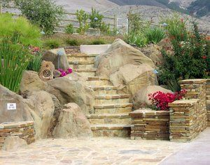 A combination of Faux boulders, flagstone covered steps and pencil rock veneered walls all retain the back slope of this backyard to allow for a in ground spa  that is located just to the left but out of the picture.