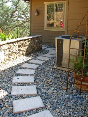 These are precast concrete column caps that we used as stepper through a deeply shaded and little used area of the landscape. To lower maintenance no plant material was used here and instead a weed barrier of non-woven fabric was laid down with the concrete stepper laid down and surrounded with a small, contrasting river washed cobble. The stone wall was made from rock found on site and the wall cap was a hand cut and chipped to contrast with the rock used on the wall.