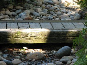 Used railroad ties provide the framework for a small wooden bridge which spans a drainage culvert that was constructed to appear as a creekbed running through the backyard.