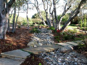 Flagstone slab bridging a dry creekbed.
