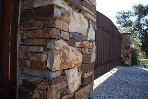 Pencil rock stone was attached to the concrete with ''thin-set adhesive to provide a drystack appearance to the pillars.
