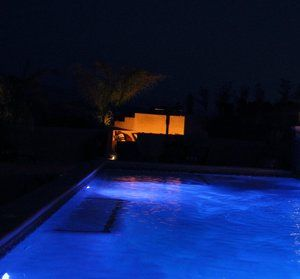 Deep cool blue coloring results from the programable LED pool lighting which contrast with the warm glow of the fire pit in the background.